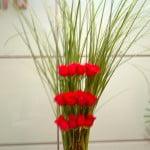 arreglo floral con Rosas rojas y follaje de Cortadera