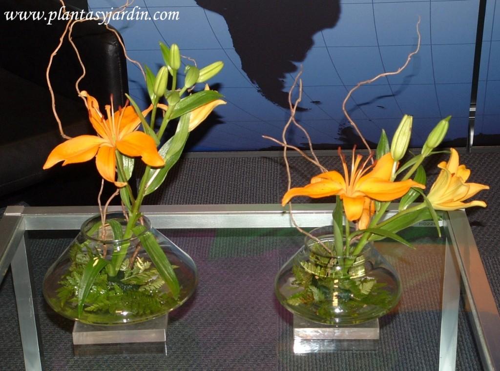 Liliums naranjas en esponja floral cubierta con follaje de helecho y Sauce eléctrico.