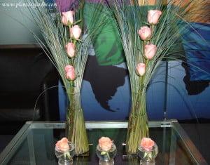 Arreglo floral en serie con rosas rosas, cortaderas verdes y azules